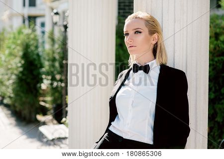 Portrait of stylish fashionable beautiful blonde woman in man black suit with bow tie outdoor