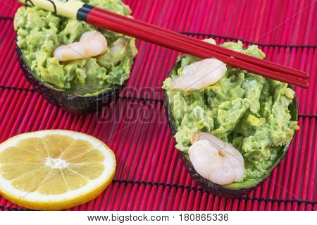 Two avocado salad with shrimps, lemon and red chopsticks on the red mat