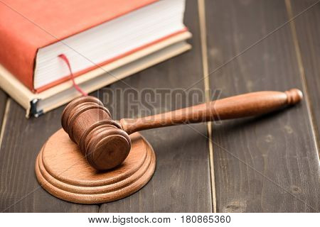 Elevated view of wooden judge hammer and book on wooden tabletop law concept