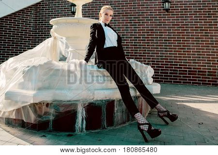 Portrait of stylish fashionable beautiful blonde woman in man black suit with bow tie outdoor nearly fountain
