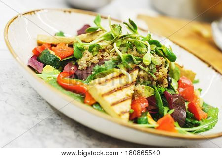 Delicious vegetarian salad with tofu and vegetables. A plate of tasty and healthy food - vitamins and health. Soft focus.