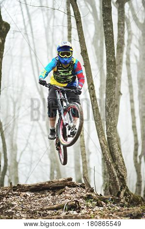 A mountain bike rider jumps from a springboard in a foggy forest, in the Caucasus Mountains, downhill riders