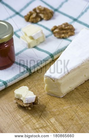 Palatable brie cheese with nuts, jam on the white towel with stripes