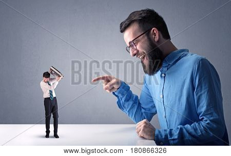Young professional businessman being angry with an other miniature businessman in front of a blueish grey background