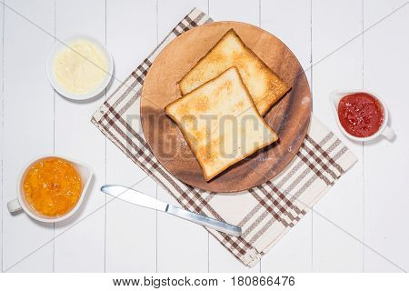 Close-up Of Slice Of Toast Bread With Jam And Butter On Wood Table