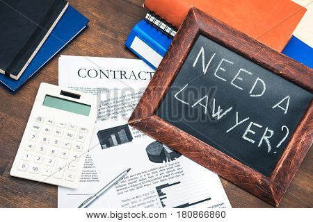 Documents, Smartphone, Calculator And Chalkboard In Wooden Frame With Text - Need A Lawyer? On Woode