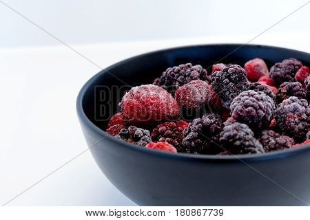 Frozen Berries in black bowl on white surface