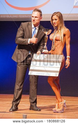 MAASTRICHT THE NETHERLANDS - OCTOBER 25 2015: Female bikini figure models celebrates her victory with officials at the World Grandprix Bodybuilding and Fitness of the WBBF-WFF