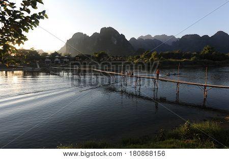 Vang Vien, Laos - 15 January 2012: People walking on the bridge over the river near the village of Vang Vien