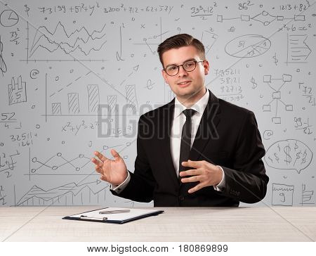 Young handsome businessman sitting at a desk with white charts behind him