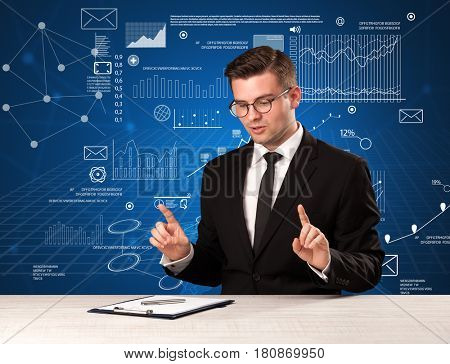 Young handsome businessman sitting at a desk with blue charts and data behind him
