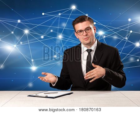Young handsome businessman sitting at a desk with a blue connection graphic behnid him