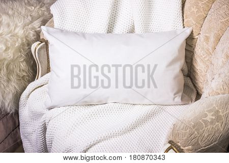 White lumbar pillow on an armchair case Mockup. Interior photo