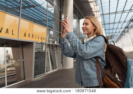 Cheerful girl taking selfie by mobile. She locating near airdrome
