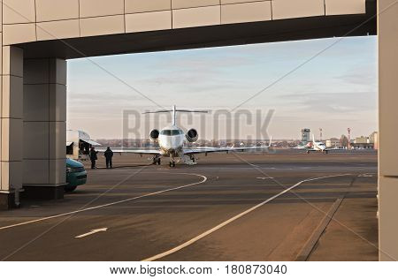 Airport employees fueling plane before departure. It standing on undercart