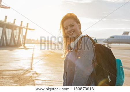 Waist up portrait of woman expressing gladness while locating at airport. She going to plane