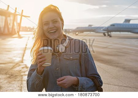 Portrait of half length cheerful girl drinking coffee. She standing at flying line near airdrome