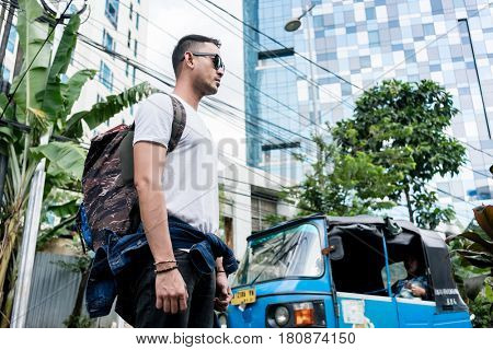 Low angle side view of a young man wearing sunglasses and backpack on a street during vacations in Indonesia