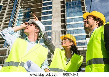 Team of architects and civil engineers inspecting construction site
