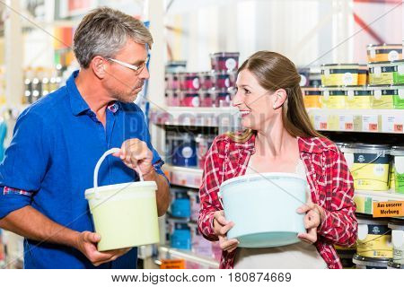Home improvement couple, woman and man, in hardware store arguing about color of paint for renovating