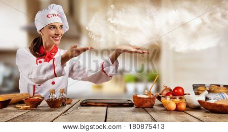 Young chef woman cooker gesturing on copyspace. Raw ingredients served on wooden table, blur modern kitchen on background