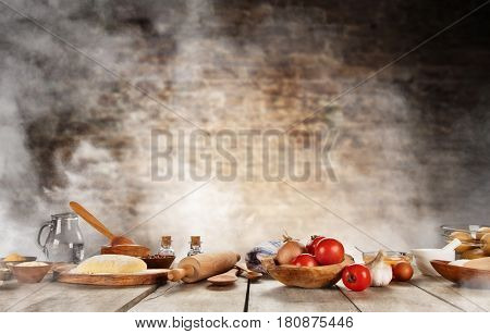 Baking ingredients placed on wooden table, ready for cooking pizza. Copyspace for text. Concept of food preparation, brick wall on background.