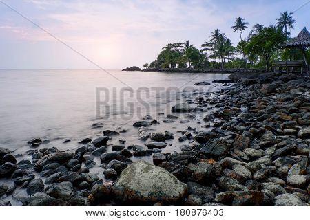 Morning sun at sea in Thailand. Big boulders sticking from smooth wavy sea. Sea at Bai Lan Beach : Koh Chang .