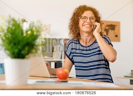 Middle aged woman at office making a phone call