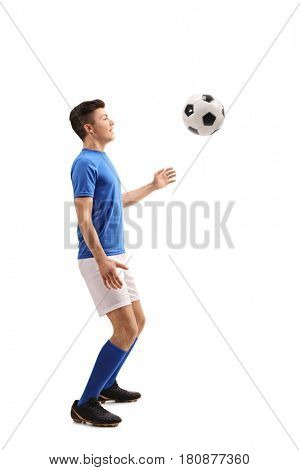 Full length profile shot of a teenage soccer player with a football isolated on white background