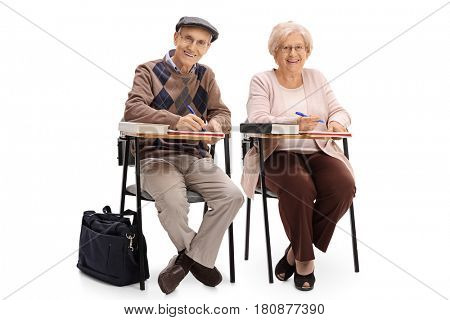 Two elderly students sitting in school chairs and taking notes isolated on white background