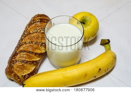 Pastry Banana Aplle and Glass of Milk Isolated on White Background. Healty breakfast roll with sesamo and glass of fresh milk. Backery bread breakfast.
