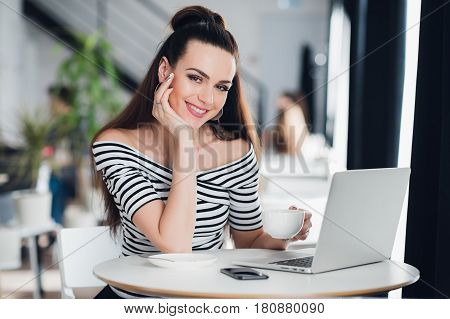 Young beautiful business woman working on her laptop indoors, smiling adult woman is using a laptop in sidewalk cafe, smiling girl with laptop computer in cafe