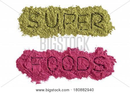 Superfoods word with green and pink powders isolated on white. Healthy food supplements detox concept. Flat lay