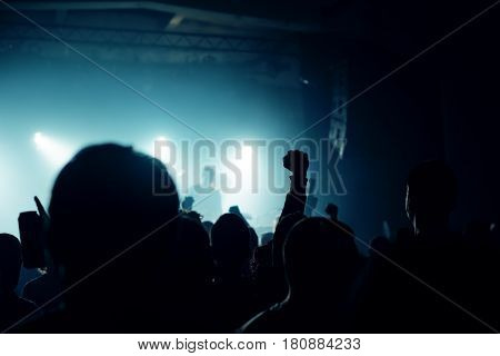 Music concert fans crowd people at popular live rock performance hands in the air selective focus