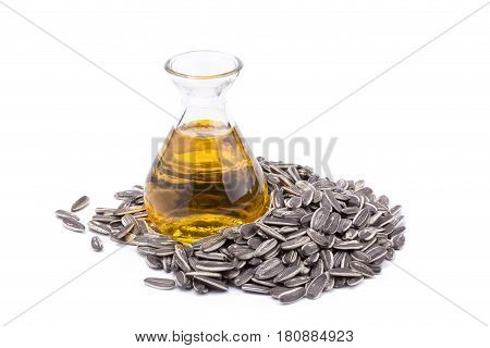 Sunflower oil in glass bottle and sun-flower seed isolated on white background.