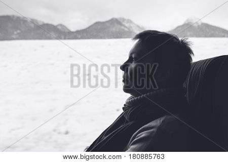 Female tourist on the bus riding through winter mountain landscape monochromatic black and white image