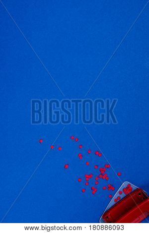 top view of red puncher and paper pieces on blue