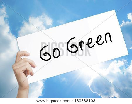 Go Green Sign on white paper. Man Hand Holding Paper with text. Isolated on sky background. Business concept. Stock Photo