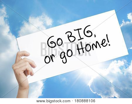 Go Big or Go Home Sign on white paper. Man Hand Holding Paper with text. Isolated on sky background. Business concept. Stock Photo