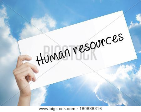 Human resources Sign on white paper. Man Hand Holding Paper with text. Isolated on sky background. Business concept. Stock Photo