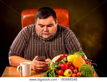 Diet fat man eating healthy food . Healthy breakfast with vegetables for overweight person. Male trying to lose weight but orders fast pizza by phone. Concept on black background.