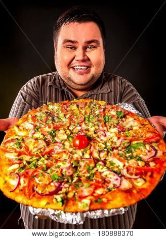 Fat man eating fast food and offers great pizza to customers . Breakfast for overweight person. Junk meal leads to obesity. Person regularly overeats concept on black background.