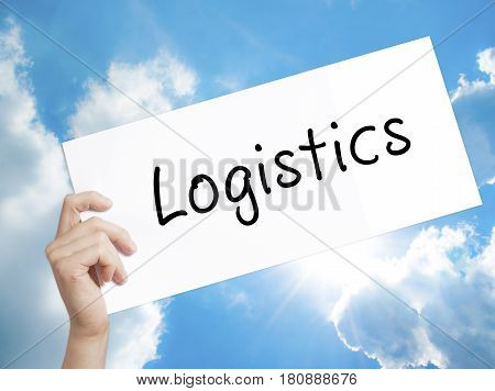 Logistics Sign on white paper. Man Hand Holding Paper with text. Isolated on sky background. Business concept. Stock Photo