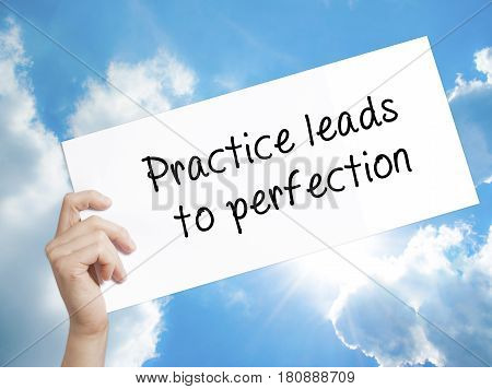 Practice leads to perfection Sign on white paper. Man Hand Holding Paper with text. Isolated on sky background. Business concept. Stock Photo