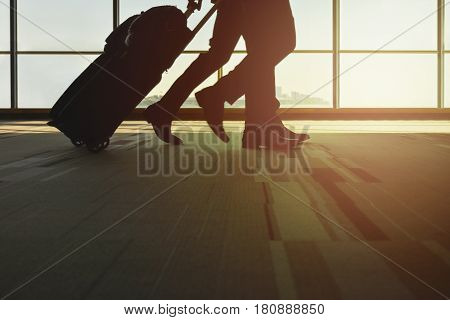 Silhouette traveller with luggage walking in the airport