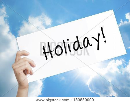 Holiday! Sign on white paper. Man Hand Holding Paper with text. Isolated on sky background. Business concept. Stock Photo