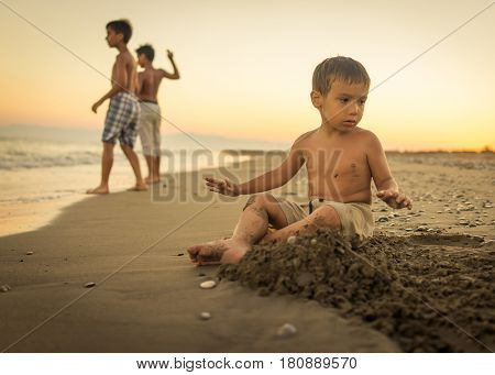 Happy child playing and building in the beach sand
