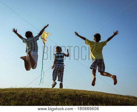 Children running kite on meadow with beautiful sky cloud above
