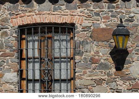 Detail of window with iron grate and iron lantern on stone wall