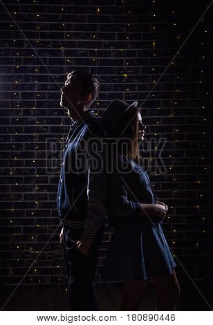 Silhouette photo of teen couple standing against dark brick wall decorated by yellow lights garland